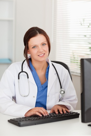 A female doctor is typing on her keyboard and looking photo