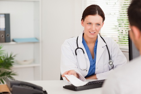 A female doctor is giving a patient a prescription Stock Photo - 11232186