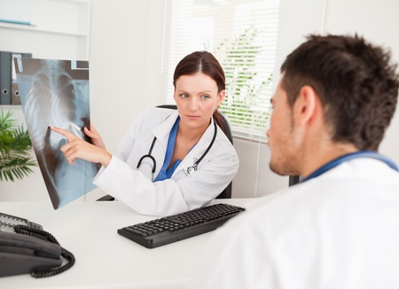 A female doctor is showing another doctor a x-ray photo