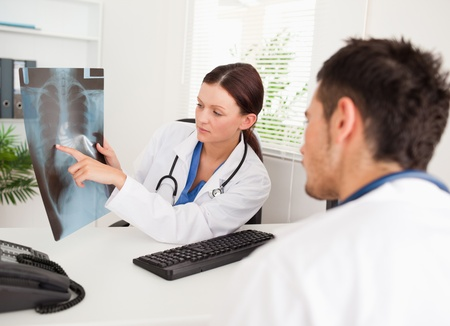 A female doctor is showing another doctor something on a x-ray  photo