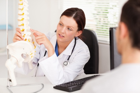 A female doctor is pointing on a bone in a spine photo