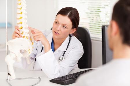 fisico: Una doctora que apunta a un hueso en la columna vertebral Foto de archivo