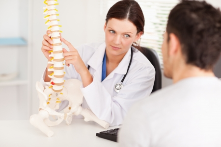 A female doctor is showing a doctor a spine photo
