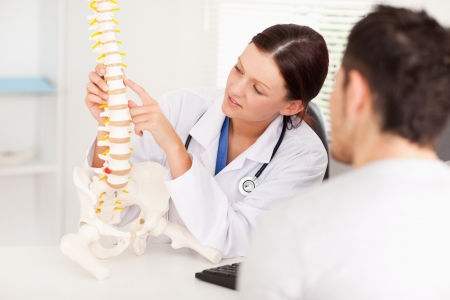 A female doctor is pointing on a bone in the spine photo