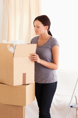 A woman is packing a cardboard photo