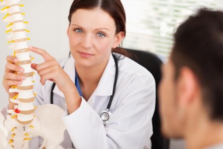 columna vertebral: Una doctora se muestra a un paciente una columna Foto de archivo