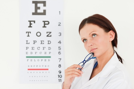 A female optician with eye test in her office Stock Photo - 11211989
