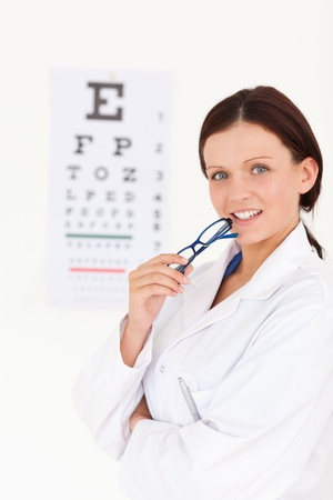 A gorgeous female optician with an eye test in her office photo