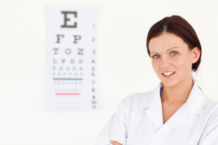 A nice female optician with an eye test in office photo