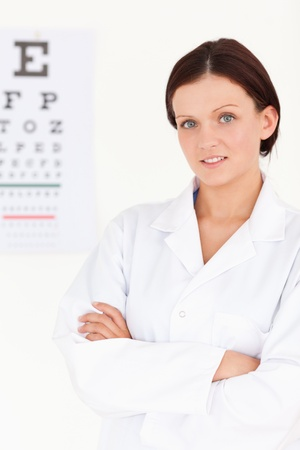 A female optician with crossed arms and eye test photo