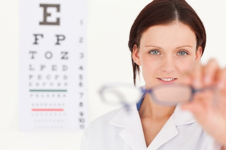 oculist: A female optician with eye test showing glasses