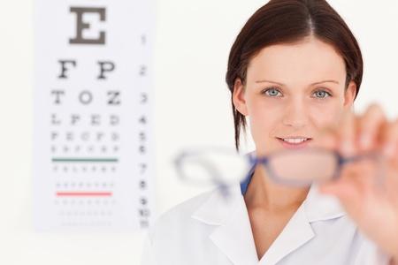 oculista: Un �ptico femenino examen de la vista que muestra las gafas