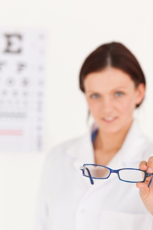 A blurred female optician showing glasses photo