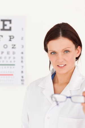A female optician showing glasses next to an eye test photo