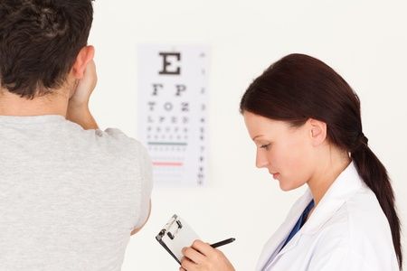 A female optician and a patient using an eye test photo