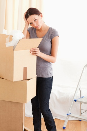 A female is packing a cardboard in the living room photo