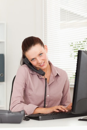 A businesswoman with a phone is typing in her office photo