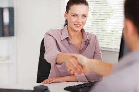 A businesswoman is shaking hands with a customer photo