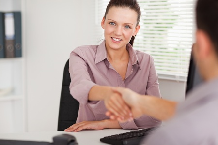 A businesswoman shakes hand with someone photo