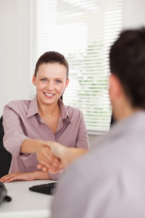 happy client: A businesswoman shakes hands with a man in her office