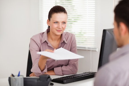 handing: A businesswoman is presenting a contract to a customer