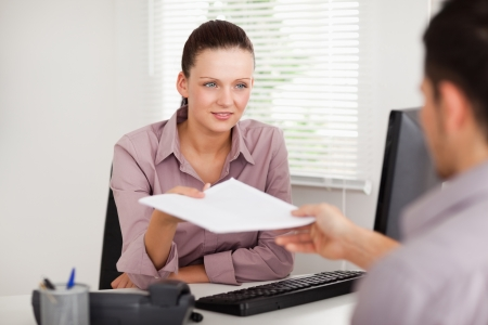 woman with document: A businesswoman is presenting a contract to a customer