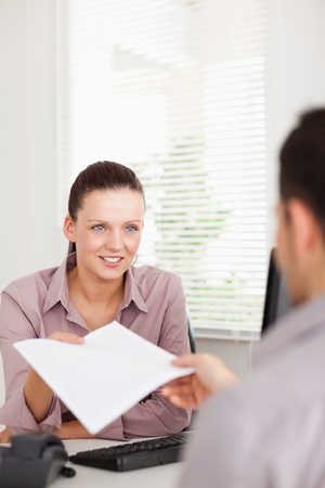 handing: A businesswoman presents a contract to a customer