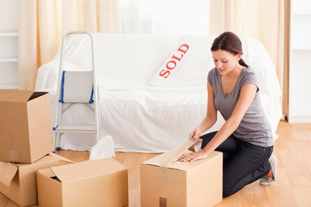 packing: A female is preparing cardboards for the transport