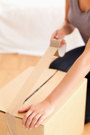 A close up of a female preparing a cardboard for transport photo