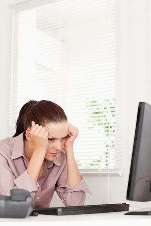 A frustrated businesswoman sitting in her office photo