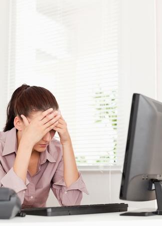agotado: Una mujer de negocios frustrados sentada en su oficina