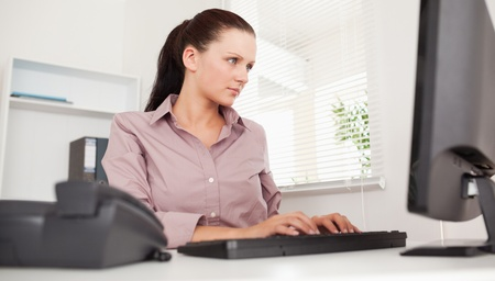 A businesswoman is typing on her keyboard photo