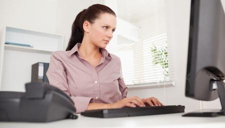 typing: Una mujer de negocios est� escribiendo en su teclado Foto de archivo