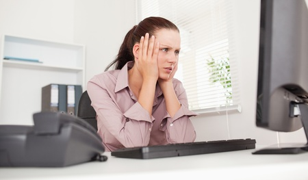gorgeous businesswoman: A stressed businesswoman is looking to the screen of her pc