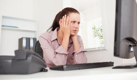 Een benadrukt zakenvrouw is op zoek naar het scherm van haar pc
