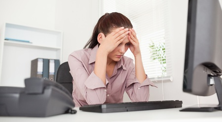 worried: A frustrated businesswoman sitting in her office Stock Photo