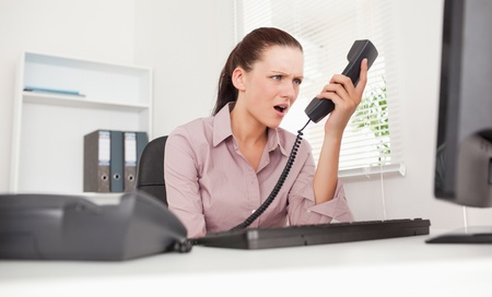 A depressed businesswoman shouting at telephone in her office photo