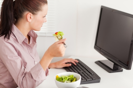 A businesswoman eats salad in her office whilst typing photo