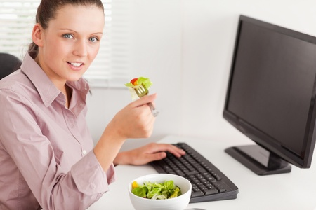 A businesswoman eating salad in her office photo
