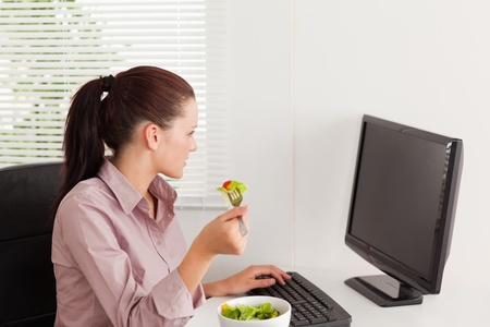 A businesswoman is eating salad whilst typing and looking to screen of her pc photo