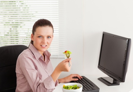 A businesswoman eats salad in her office photo