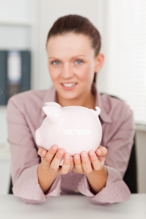A businesswoman holds a piggy bank in her office photo