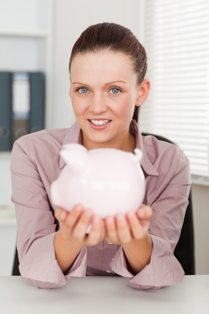 A businesswoman is holding a piggy bank in her office photo