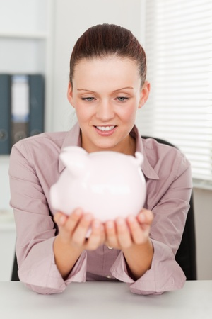 A businesswoman holds a piggy bank at her workplace photo