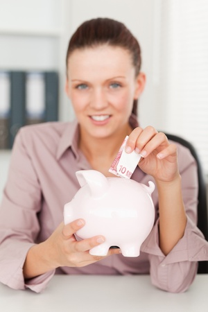 A businesswoman putting money into her piggy bank photo