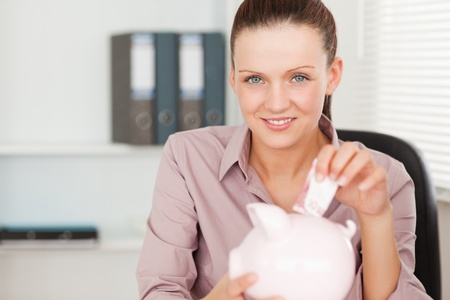 A female inserting money into her piggy bank photo