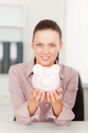 A businesswoman holding her piggy bank in her office photo