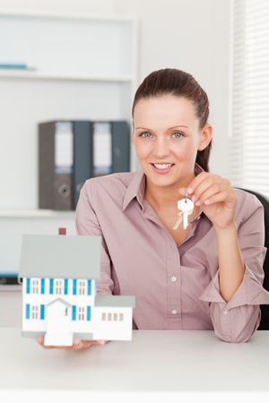 A businesswoman is showing a pair of keys and a model house Stock Photo - 11192008