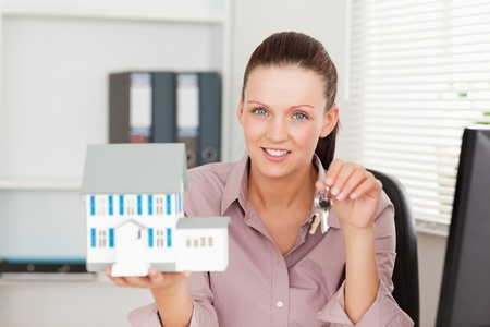A businesswoman is showing keys and a miniature house Stock Photo - 11192302