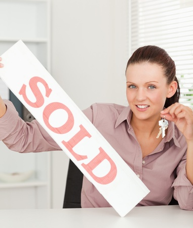 A businesswoman is holding keys and a sold sign photo